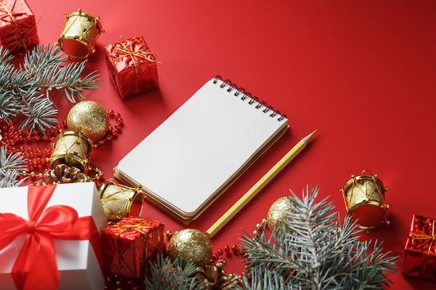 Blocco note e matita per scrivere auguri e regali per il nuovo anno e il natale intorno alle decorazioni dell'albero di natale Foto Premium