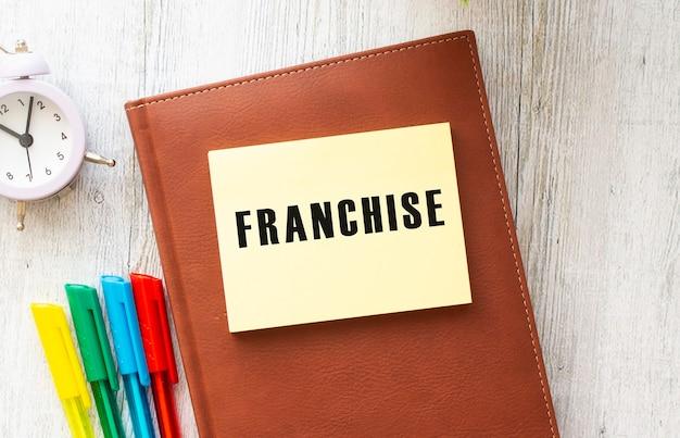 Blocco note con testo franchising su un bianco, vicino a laptop, calcolatrice e forniture per ufficio Foto Premium