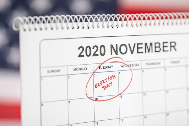 3 novembre 2020 il giorno delle elezioni concetto. calendario da tavolo con 3 novembre contrassegnato in rosso e bandiera usa sullo sfondo Foto Premium
