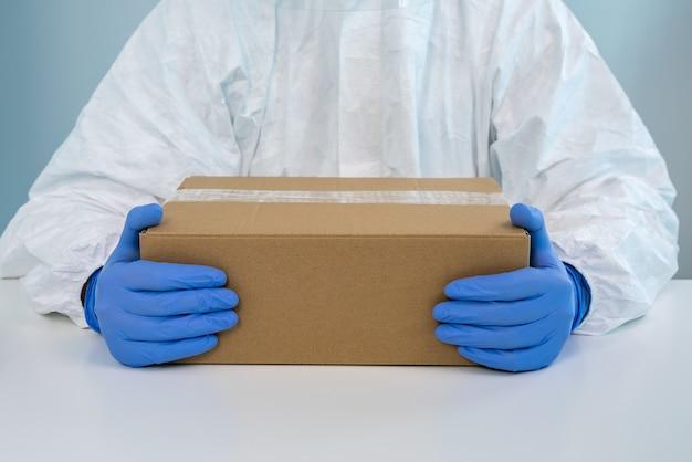 L'infermiera in tuta protettiva mostra una scatola con entrambe le mani in ospedale. l'operatore sanitario riceve forniture mediche per combattere il covid 19 Foto Premium