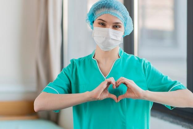 Infermiera con le mani a forma di cuore Foto Premium
