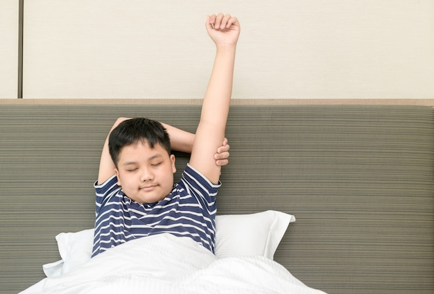 Il ragazzo grasso obeso si sveglia e si allunga sul letto la mattina, l'assistenza sanitaria e il concetto di mondo del buongiorno Foto Premium