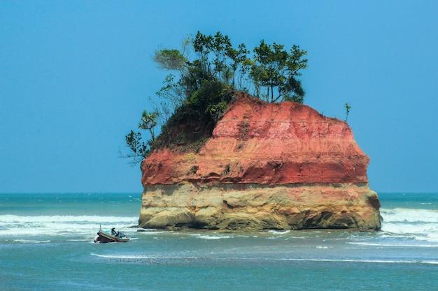 Vista sull'oceano e pescatori con la loro isola nel mezzo di un oceano blu Foto Premium