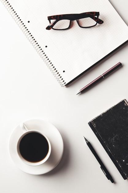Tavolo scrivania da ufficio con forniture, tazza di caffè e fiori. vista dall'alto con copia spazio Foto Premium