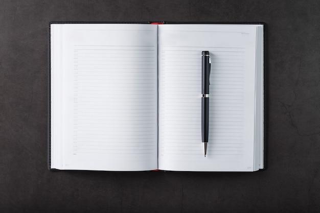 Scrivania da ufficio con blocco note nero e penna su sfondo nero. vista dall'alto con copia spazio. obiettivi aziendali e concetto di obiettivi Foto Premium