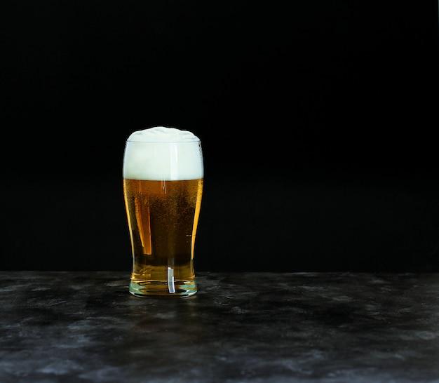Concetto del festival della birra dell'oktoberfest. birra fredda con schiuma in vetro su oscurità, copyspace. Foto Premium