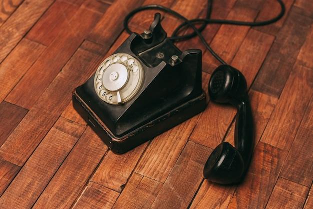 Vecchio telefono nero sul pavimento, vintage Foto Premium