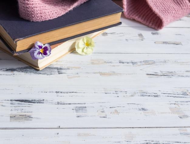 Vecchi libri e fiori sulla tavola di legno leggera. concetto di lettura. spazio copia gratuita. Foto Premium