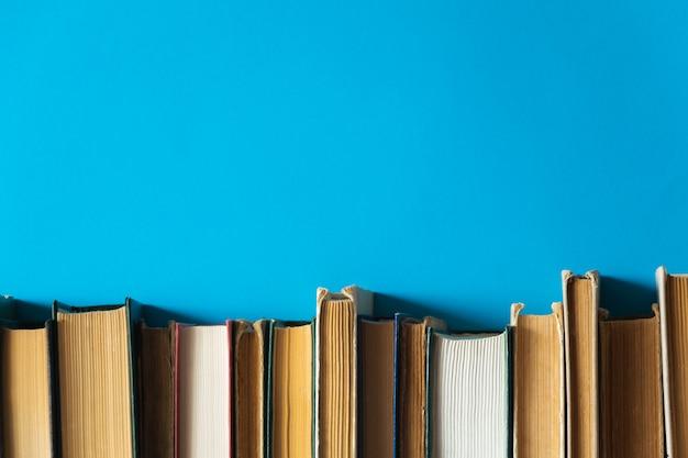 Vecchi libri su uno scaffale con sfondo blu Foto Premium