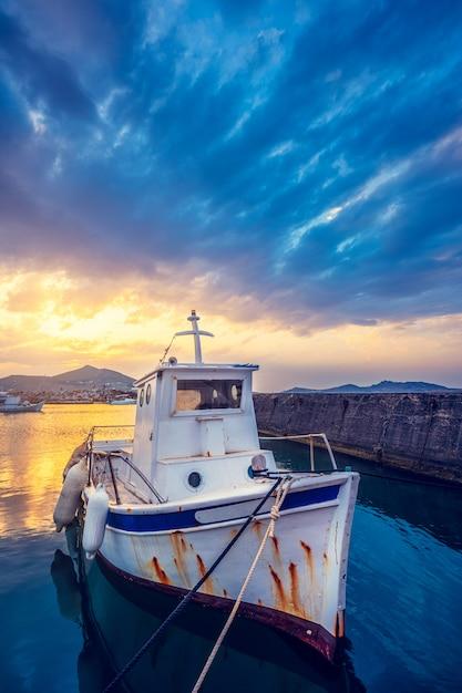 Vecchio peschereccio nel porto di naousa sul tramonto. paros island, grecia Foto Premium