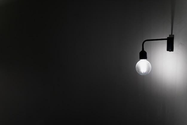Una vecchia lampadina sul muro di cemento nel buio Foto Premium