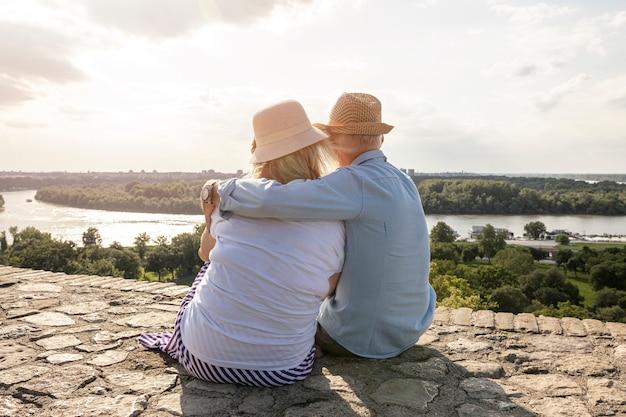 Amanti anziani che si siedono il colpo del backview Foto Premium
