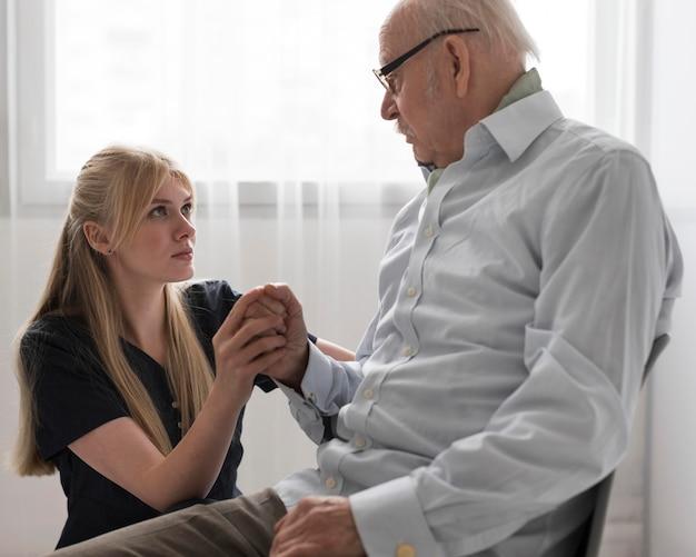 Uomo anziano che tiene la mano dell'infermiere Foto Premium