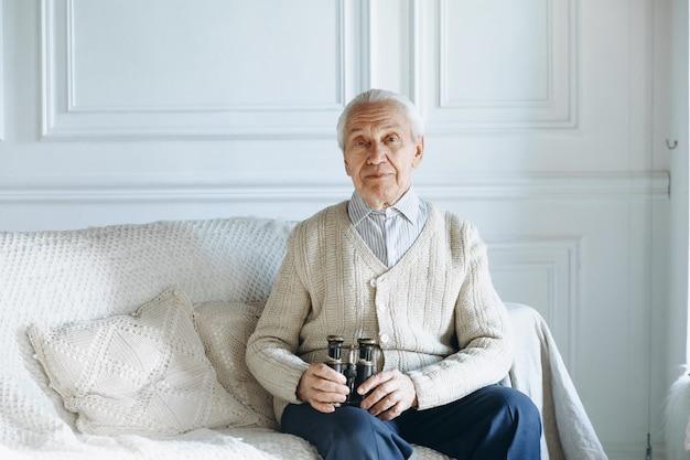 Vecchio seduto sul divano Foto Premium