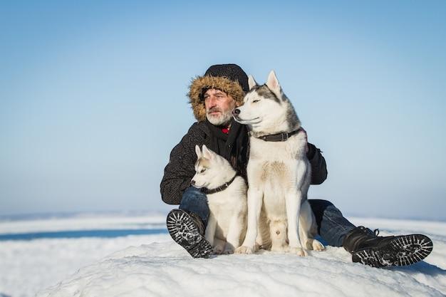 Cani di slitta e dell'uomo anziano su una banchisa. Foto Premium