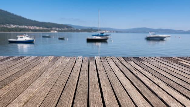 Vecchia passerella in legno in riva al mare con sfondo sfocato e barche Foto Premium