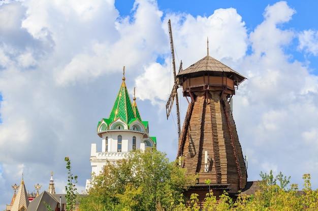 Vecchio mulino a vento in legno nel cremlino di izmailovo a mosca contro la torre di guardia nella soleggiata mattina d'estate Foto Premium