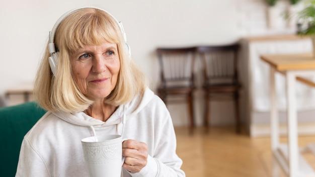 Donna anziana che gode del caffè a casa e della musica sulle cuffie Foto Premium