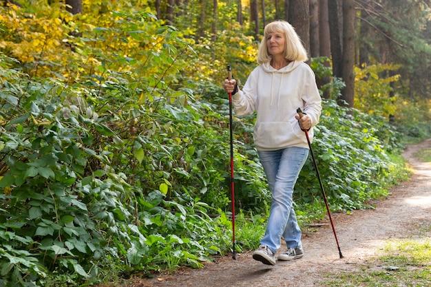 Donna anziana che fa trekking all'esterno Foto Premium