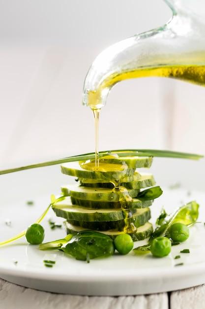 Olio d'oliva versato su insalata di cetrioli su un piatto bianco Foto Premium