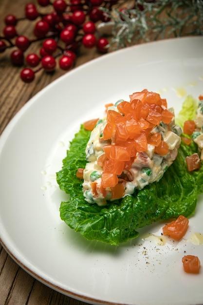 Insalata olivier con salmone su un tavolo di legno Foto Premium