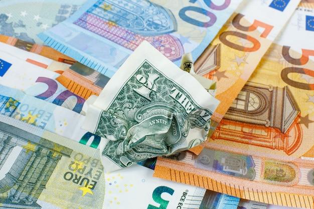 Un dollaro sgualcito è sulle nuove banconote in euro. il concetto è nuovo e vecchio. rinuncia al denaro. cambio di valuta. il denaro è carta. Foto Premium