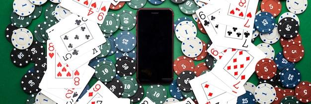 Casinò online, casinò mobile, telefono cellulare, chip card su uno sfondo verde. giochi d'azzardo. vista dall'alto. Foto Premium