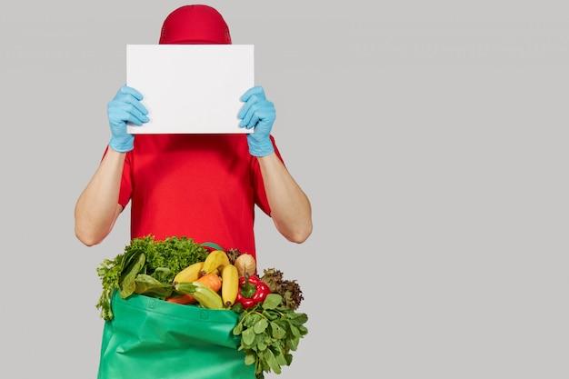 Concetto di shopping online. il corriere maschio in uniforme rossa, maschera protettiva e guanti con un contenitore di drogheria frutta e verdura fresca detiene un banner bianco per il testo. consegna a domicilio di alimenti durante la quarantena Foto Premium