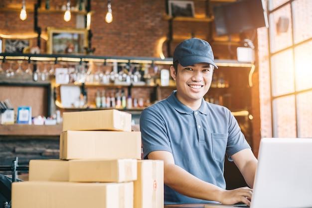 I giovani dello shopping online iniziano la piccola impresa in una scatola di cartone al lavoro. Foto Premium