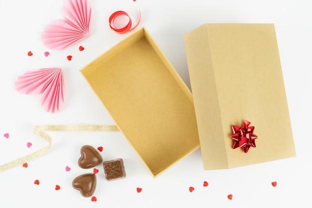Scatola di cartone aperta con decorazioni per san valentino, anniversario, festa della mamma e compleanno Foto Premium