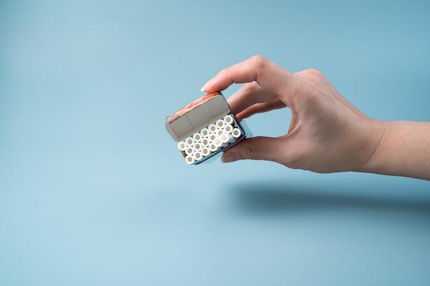 Un pacchetto di sigarette aperto in mano a una donna su sfondo azzurro. Foto Premium