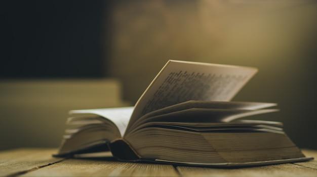 Libro aperto sul tavolo in legno, profondità di campo e colore effetto del cinema Foto Premium