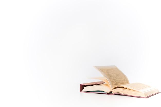 Aperto il libro del corano su bianco Foto Premium
