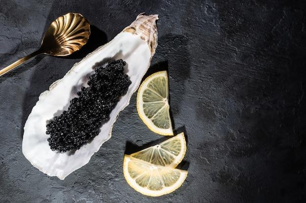 Ostriche aperte con tavolo in cemento nero di caviale nero di storione. vista dall'alto, disteso, copia spazio. Foto Premium