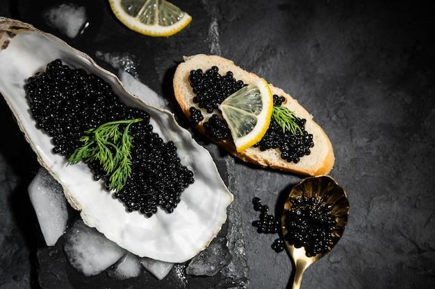 Ostriche aperte con caviale nero di storione e limone su ghiaccio sul tavolo di cemento nero. vista dall'alto, disteso, copia spazio. Foto Premium