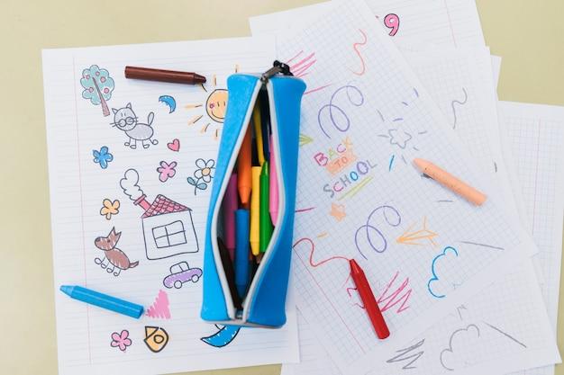 Astuccio aperto e pastelli a cera sparsi su disegni di bambini Foto Premium