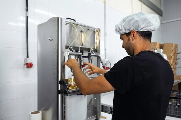 Operatore che imbottiglia manualmente nel processo di produzione kombucha in una fabbrica Foto Premium