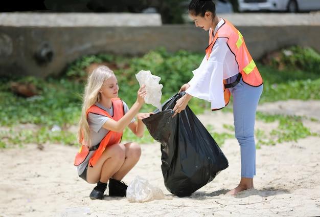 Ottimisti due volontari che tengono il sacco della spazzatura e aiutano a raccogliere la spazzatura al parco, stanno raccogliendo la spazzatura e la mettono in un sacco della spazzatura nero. Foto Premium