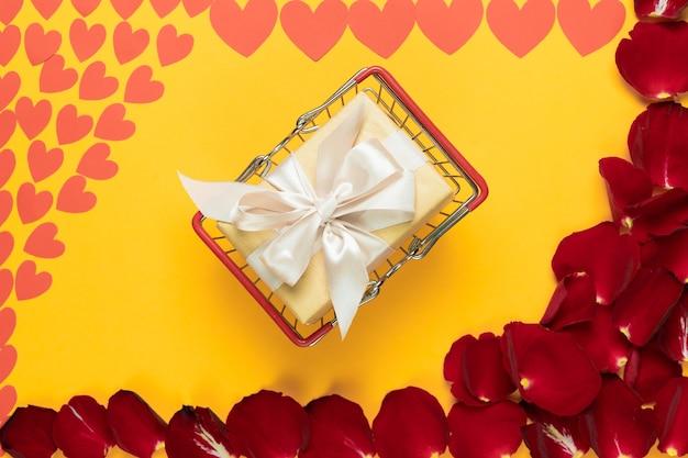 Su uno sfondo arancione per l'iscrizione si trova un cesto con un regalo a sorpresa, petali di rose rosse e cuori di carta Foto Premium