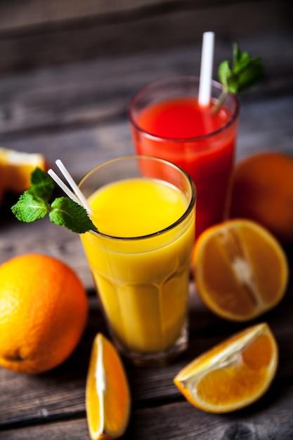 Succo d'arancia in vetro con menta, frutta fresca su legno Foto Premium