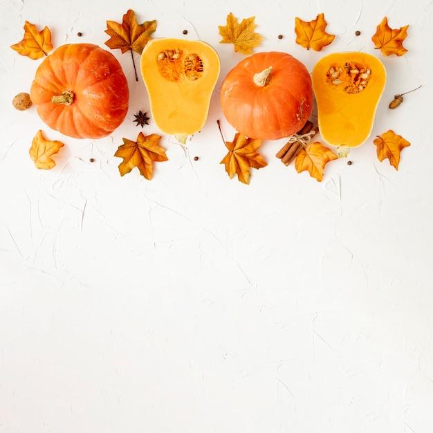 Zucche arancio sulle foglie con fondo bianco Foto Premium
