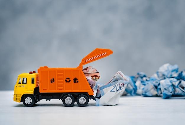 Il camion della spazzatura arancione del giocattolo scarica le banconote di carta sgualcite Foto Premium