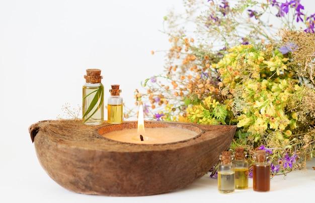 Oli aromatici essenziali biologici in bottiglie di vetro, erbe medicinali e candela ecologica. messa a fuoco selettiva Foto Premium