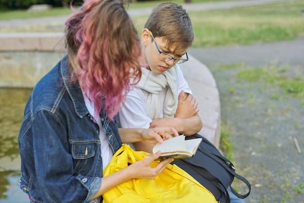 Un ritratto all'aperto di due studenti di conversazione degli adolescenti Foto Premium