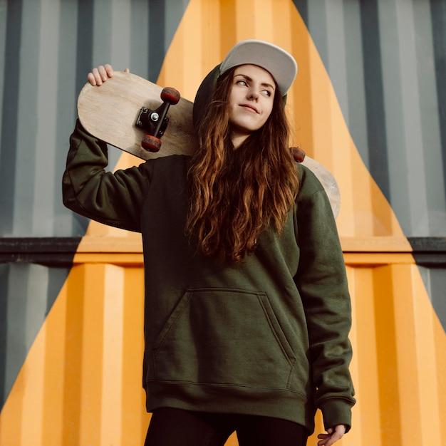 Ragazza pattinatrice all'aperto e il suo skateboard Foto Premium