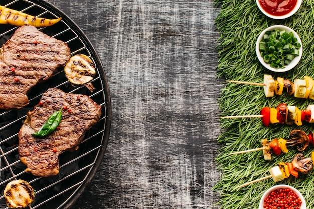 Vista dall'alto di gustosa bistecca alla griglia e spiedino di carne con ingrediente Foto Premium
