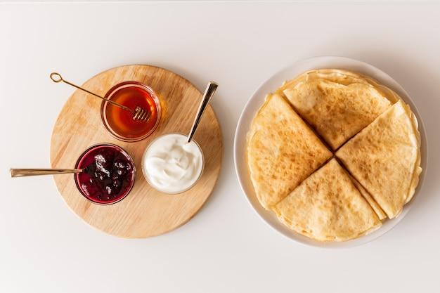 Panoramica di frittelle piegate fresche fatte in casa sul piatto e piccole ciotole di vetro con miele, marmellata di ciliegie e crema acida su tavola di legno Foto Premium