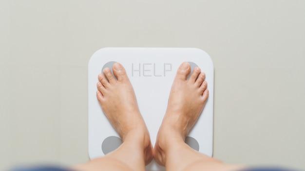 La femmina in sovrappeso è in piedi su scale bianche a casa con la parola aiuto Foto Premium