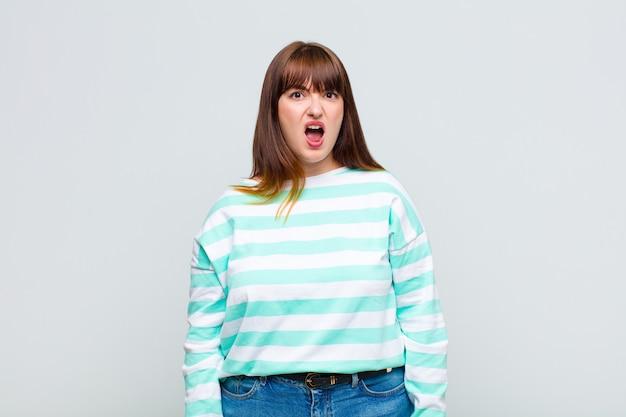 Donna in sovrappeso che sembra scioccata, arrabbiata, infastidita o delusa, a bocca aperta e furiosa Foto Premium