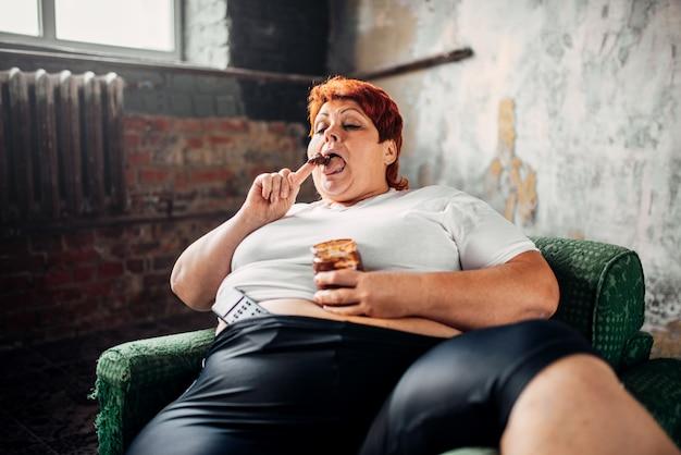 La donna in sovrappeso si siede su una sedia e mangia i dolci Foto Premium